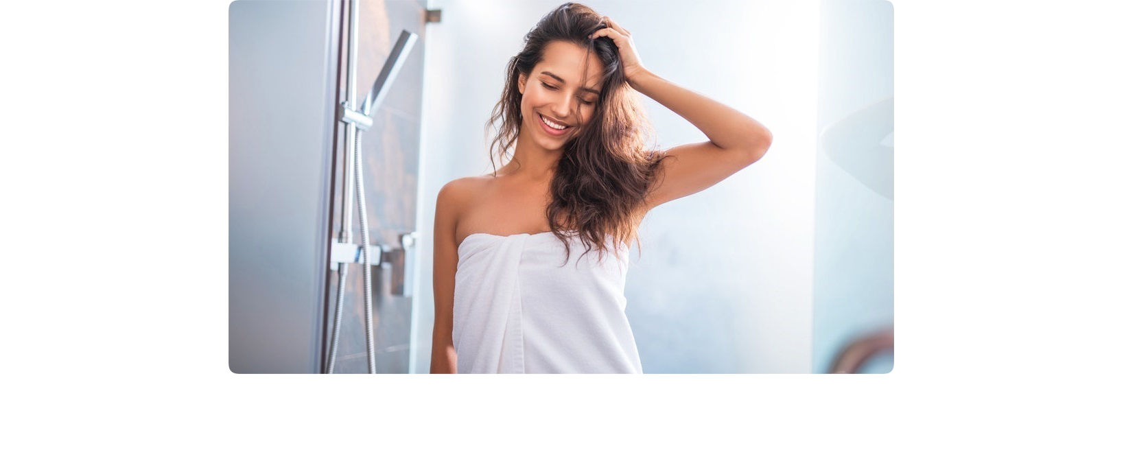 Smiling woman coming out of the shower wrapped in white towel